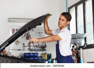 Male mechanic opening car bonnet. Side view