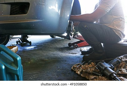 a male mechanic performing maintenance work on a car's front tyre.