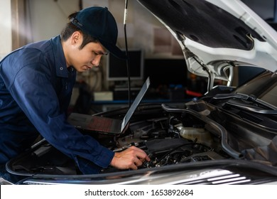 male mechanic using a laptop while repairing car in auto service