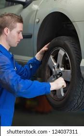 Male mechanic using lug wrench to change car tyre