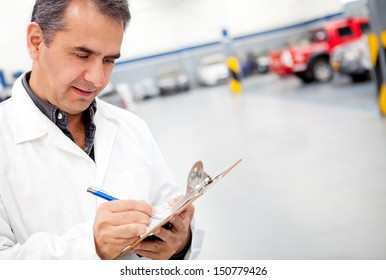 Male mechanic working at a car garage and taking notes
