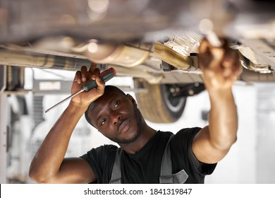 male mechanic is working on a vehicle in a car service, alone in modern clean workshop