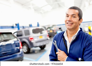 Male mechanic working at a repair shop and holding tools