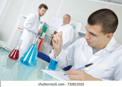 male medical laboratory young researcher performs tests with blue liquid