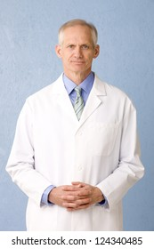 Male medical professional in lab coat on blue background three quarter length