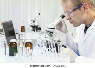 A male medical or scientific researcher or doctor using a microscope in a laboratory with test tubes.