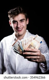 Male medicine cheerful doctor holding in hands euro banknotes.Medic salary, prestige and high paid job, education, public health business, medical insurance concept.Bribe and corruption concept