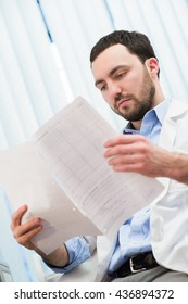 Male medicine doctor checking something at his papers. Medical care, insurance, prescription, paper work or career concept. Physician ready to examine patient and help.