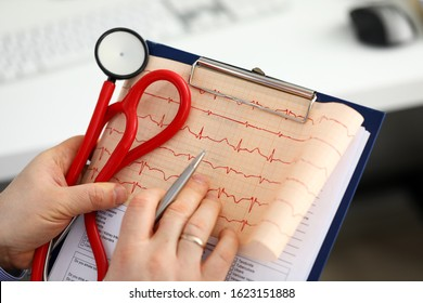 Male medicine doctor hands holding cardiogram chart on clipboard pad closeup. Cardio therapeutist assistance, physician make cardiac physical, heart rate measure document, arrhythmia concept