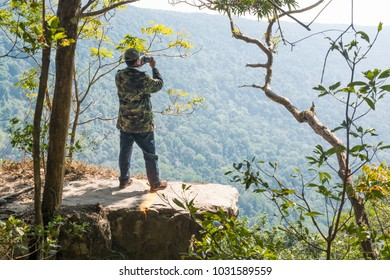 Male or Men Stand on Cliff and Take photograph of Beautiful Nature over Green Forest Mountain with Camera as Journey to Freedom Lifestyle Concept.