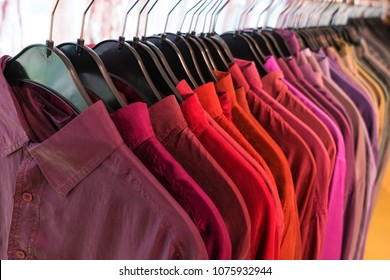 Male mens shirts sorted in color order on hangers on a shop wardrobe closet rail