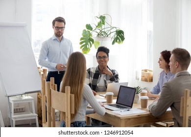 Male mentor or coach make flipchart presentation for diverse millennial employees, business speaker give training to multiracial workers working with whiteboard, mixed team brainstorming in office