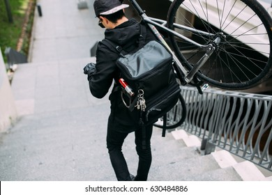 male Messanger riding fixed gear fixie bicycle around urban city of barcelona, spain with large black backpack bag making deliveries in soft light