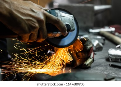 Male metal worker polishing and finalizing piece of medieval armour suit. Man hands treating metal parts of hardware in a workshop with angle grinder