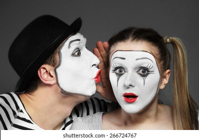 Male mime sharing secret with surprised female mime - Shutterstock ID 266724767