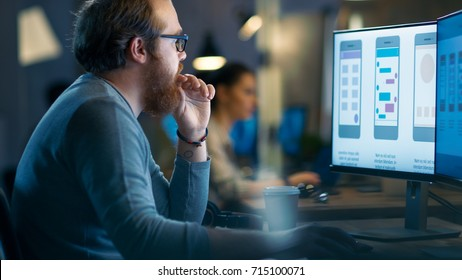 Male Mobile Application Developer Works with Graphics on His Personal Computer with Two Monitors. He Shares Office Loft with Other Creative People.