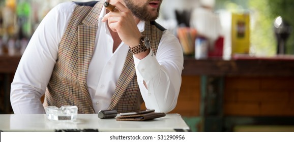 Male model with a cigar in a bar