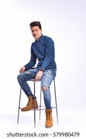 Male model in denim sitting on the chair on white . Studio shot.
