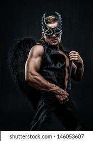 Male model dressed as deamon in a mask