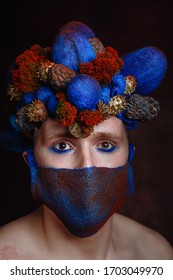 Male model with an egg - shaped headdress made of cones. Model with a multi-colored fabric mask on her face