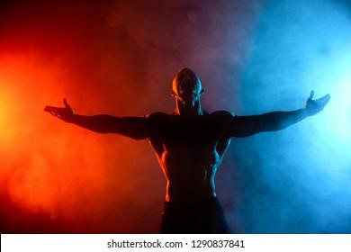 male model flexing muscles in smoke