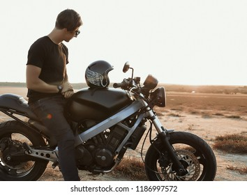Male model on the motorcycle, riding across the desert, helmet with thw wings, accessories, sun glasses, sand, tires, risky, free, outdoor, freedom of the soul, looking on sunset