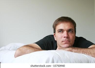 Male model on white mattress, daydreaming.
