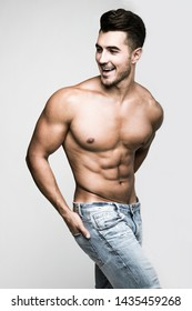 Male model with perfect body in jeans posing over grey background. Close-up. Studio shot.