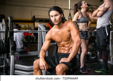 Male model with perfect muscular definition, abs, arms, biceps, chest, at the gym during workout