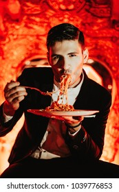 Male model in a red room decorated with hearts eating spaghetti with tomato sauce