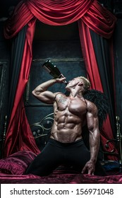 Male model Serge Henir with wings and a bottle