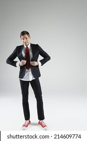 Male model smiling trying to button small sized suit on white background