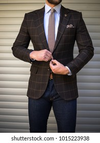 Male model in suit buttoning his jacket and posing in front of background