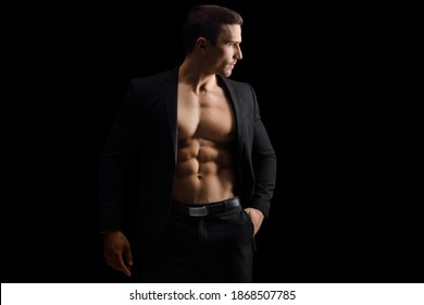 Male model with a suit and naked torso on a black background