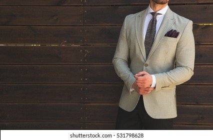 Male model in a suit posing in front of a wooden wall
