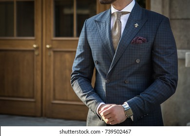 Male model in a suit posing in front of wooden doors with he's hands crossed