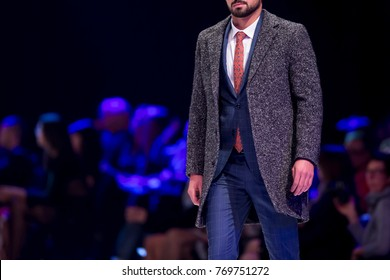 Male model walks the runway in stylish suit during a Fashion Show. Fashion catwalk event showing new collection of clothes. Single model. Blue background.