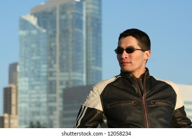Male model wearing leather motorcycle jacket with city skyline in background.