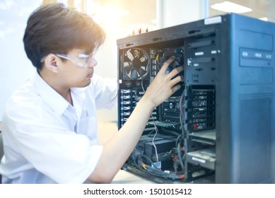 Male motherboard repairer using a screwdriver to replace the motherboard Concept of computer repair, close-up view of hardware