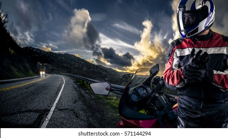Male motorcyclist wearing protective leather racing suit with a red bike or motorcycle on an open road.  The image is shot in HDR and composite.  The image depicts travel and adventure.
