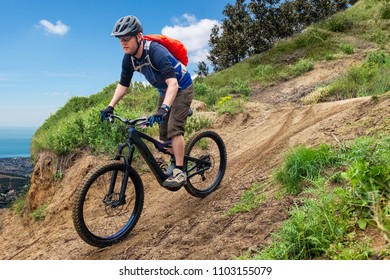 Male mountain biker on a black ebike driving downhill a dirt-track on a mountain in Spain