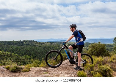 Male mountain biker on ebike standing on top of a hill, looking left