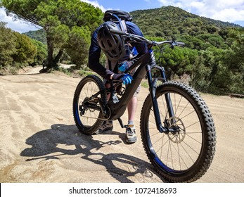 Male mountain biker tightening a screw on his ebike