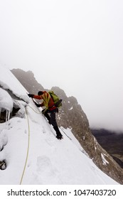 male mountain climber crossing and climbing a very steep glacier in Peru during bad weather