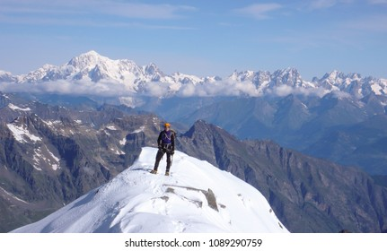 male mountain climber on the summit of Gran Paradiso with a great view of Mont Blanc behind him