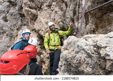 A male mountain guide instructs young climbers at the start of a steep Via Ferrata in the Dolomites of northern Italy in Alta Badia