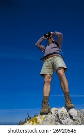 A male mountaineer observing trough binoculars over a mountain summit