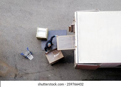 Male mover unload furniture and boxes from moving truck. Situation with moving house worker, manually download the furniture from a back of a truck. View from above.