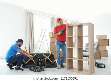 Male movers assembling furniture in new house