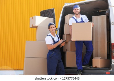 Male movers unloading boxes from van outdoors
